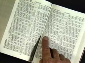 open bible with finger pointing to scripture